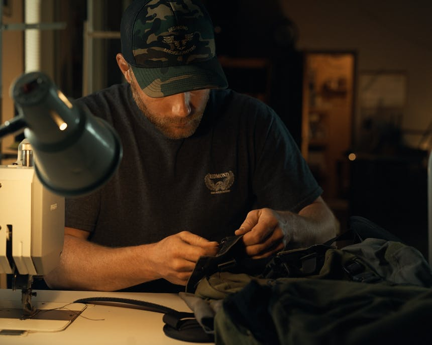 Smokejumper works on gear at sewing machine table