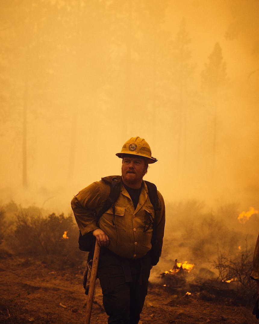 fire fighter in hard hat stands in smoky flaming field with hand on shovel