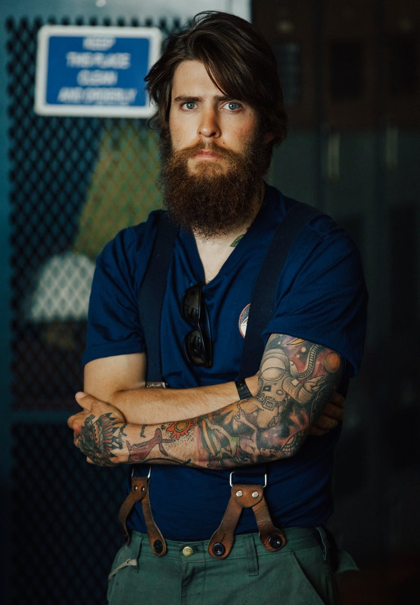 hotshot crew member portrait of man in suspenders with tattoos and blue shirt