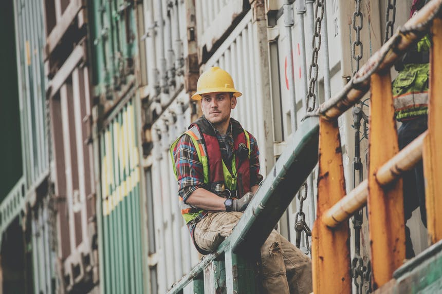 man in hard hat and safety vest sits on railing next to stacked shipping containers