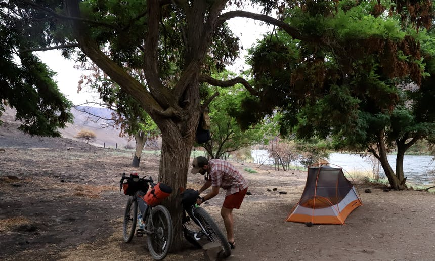 man working on bike resting on tree at campsite near river