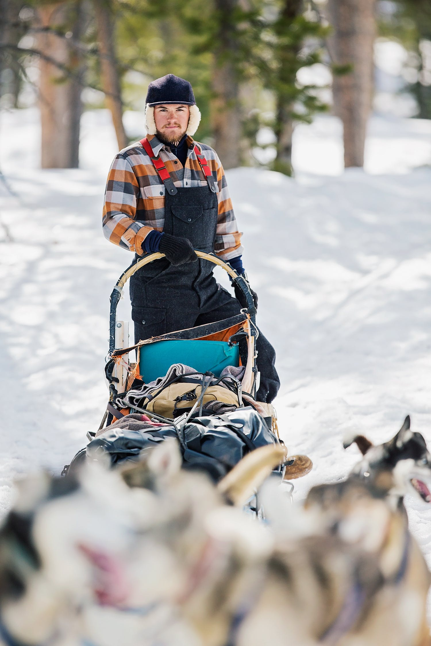 Portrait of Elliot Anderson with his sled dog team, wearing Filson clothing.