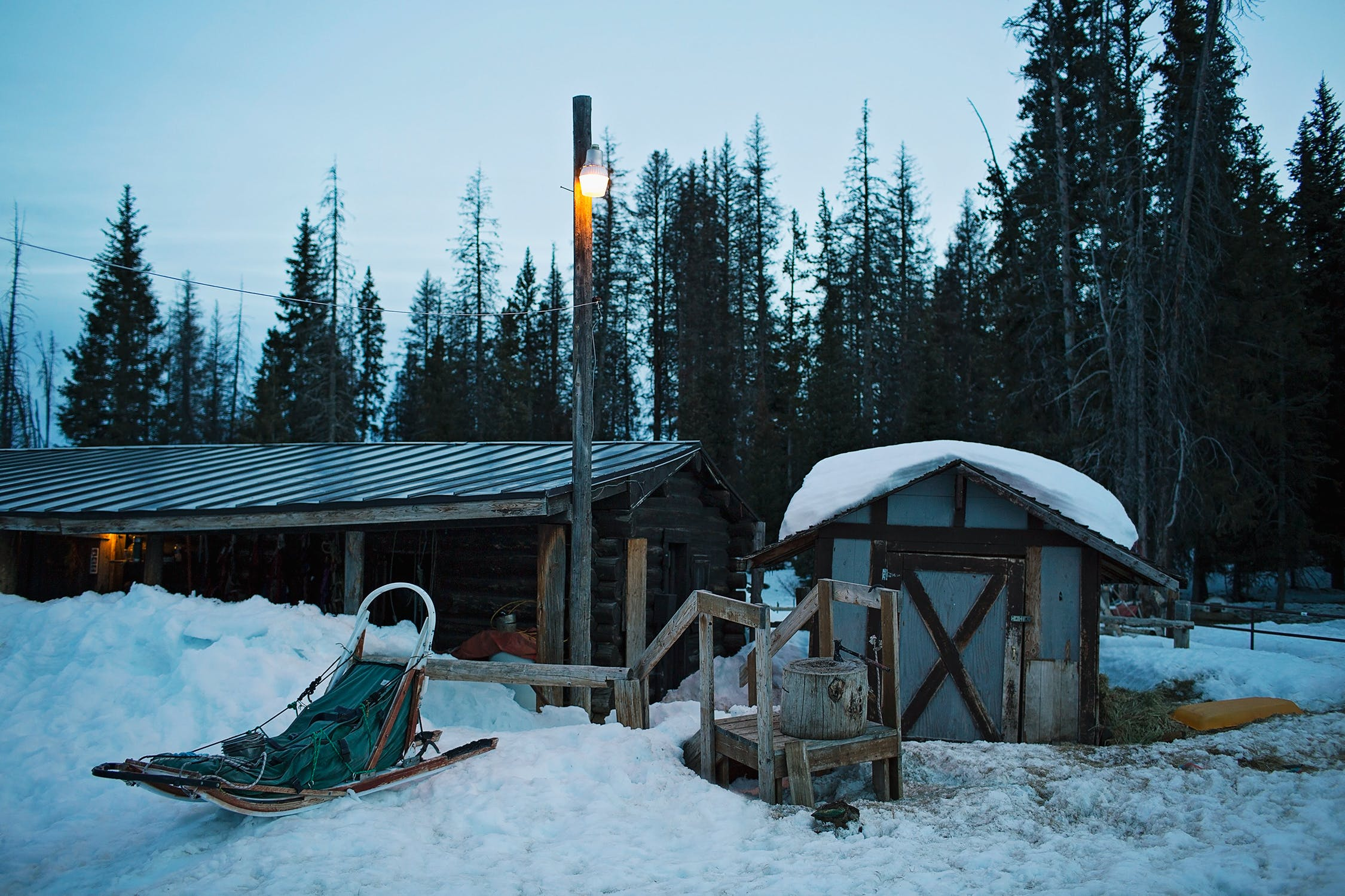 Wooden structures in a rural, winter landscape. An empty dog sled sits on the snow to the left of the frame.