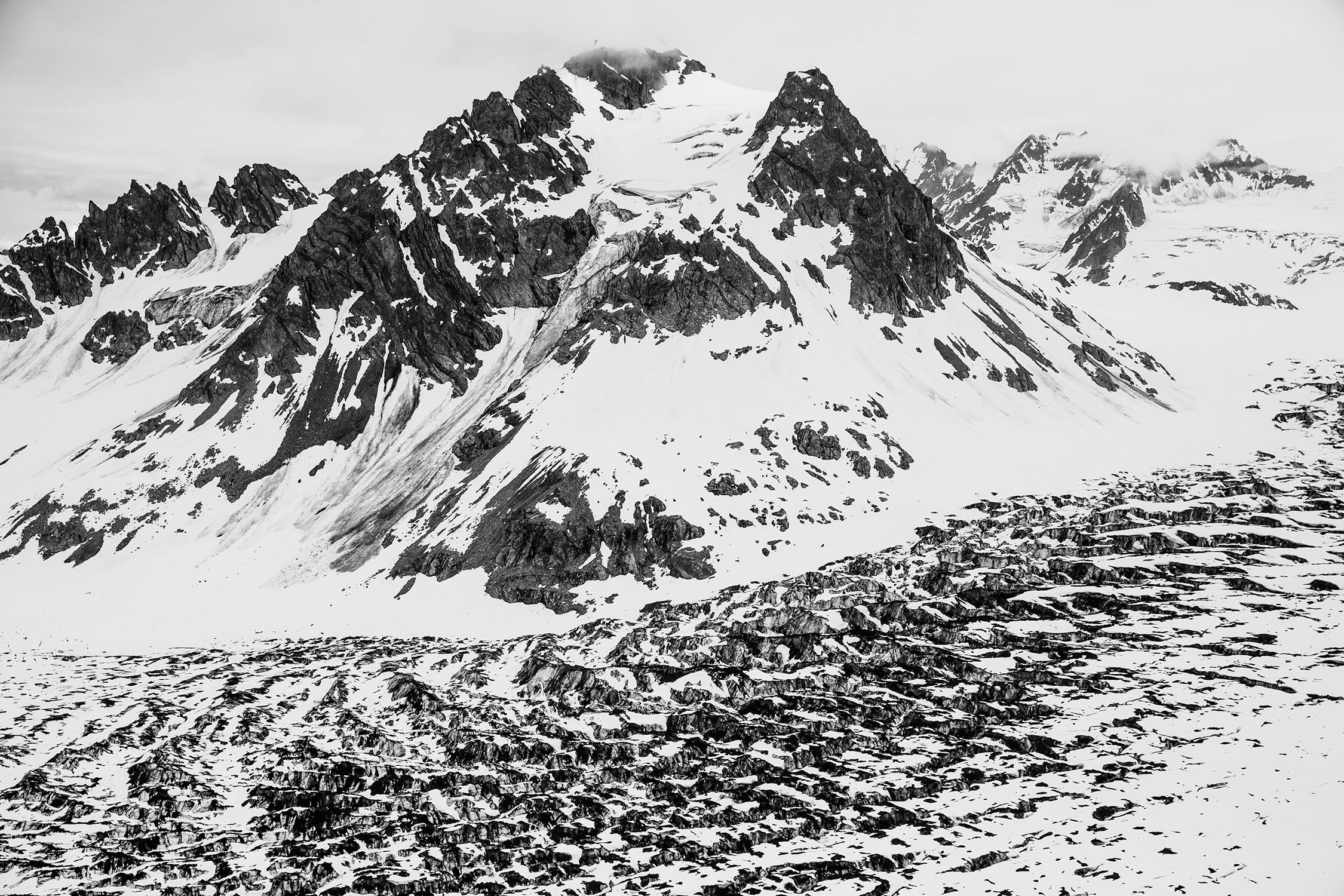 Black and white photo of a mountain and boulder field covered in snow.