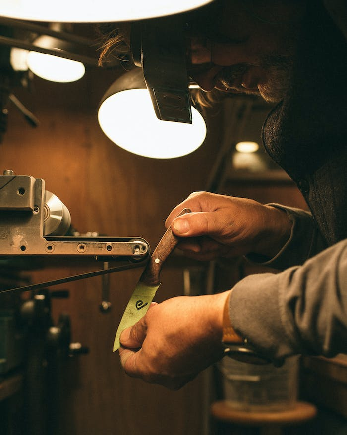 close up of man wearing protective eyewear sharpening knife in a workshop