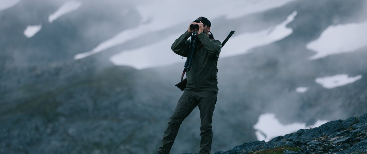 brett searching through binoculars on stone outcropping