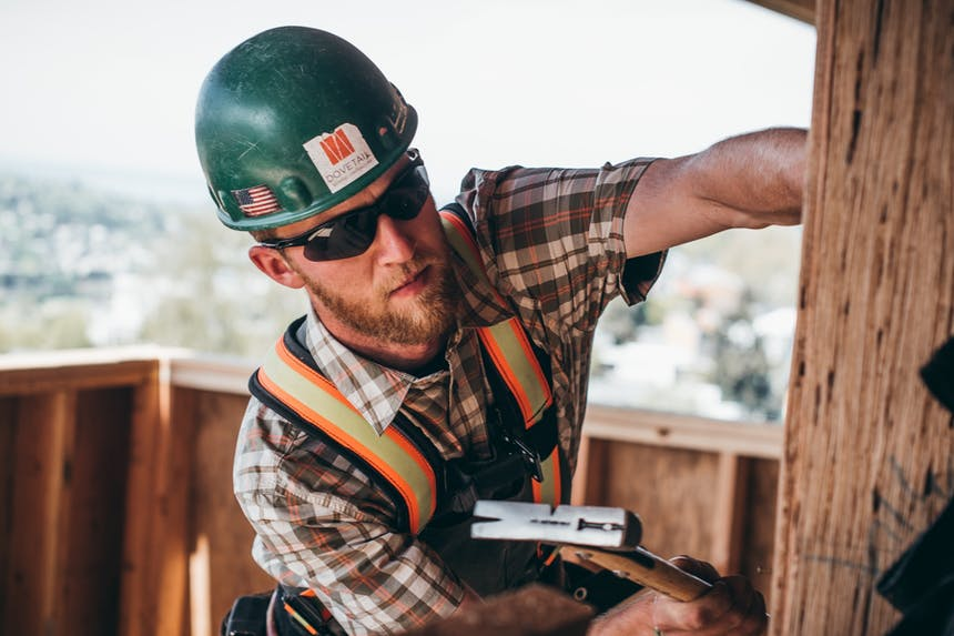 man performs carpentry work on exterior of wooden structure