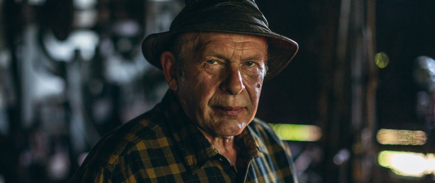man in yellow and blue plaid shirt and brown leather hat in metal shop