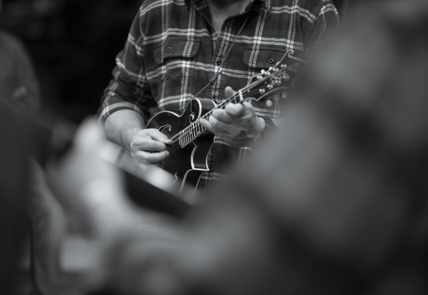 man playing mandolin in plaid shirt