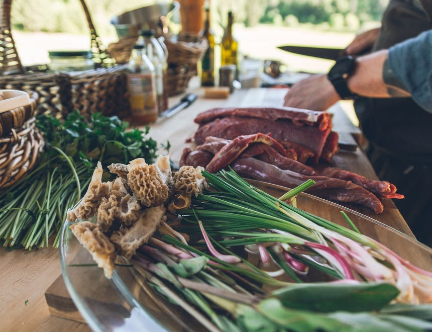 food prep with gathered herbs and mushrooms and meat being cut