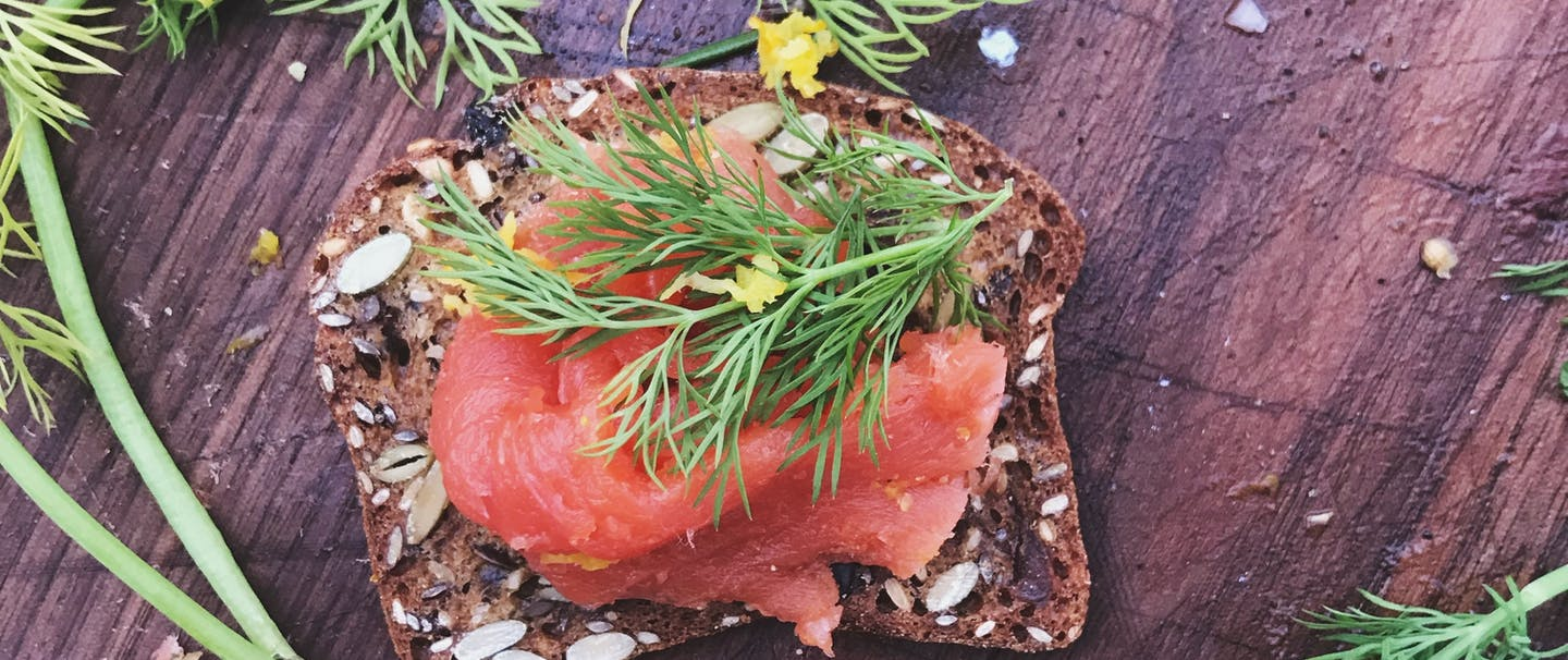 salmon gravlax with green herbs on wood cutting board
