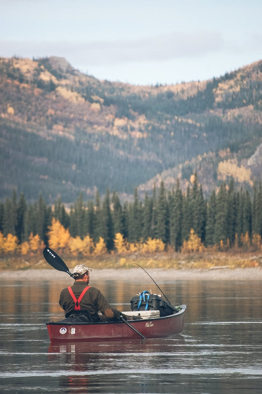 man in a canoe on the Yukon river, a large mountain in the distance