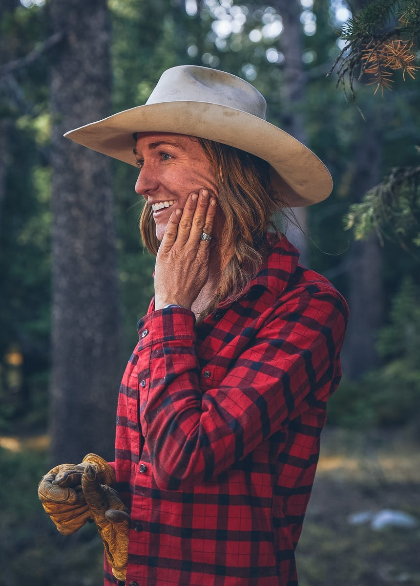 Jessie with hand on cheek in red plaid shirt in forest