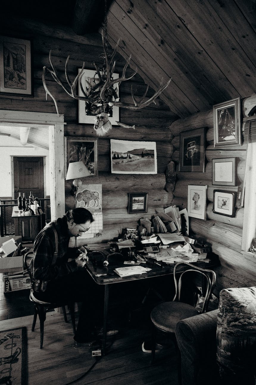 man works at desk in cabin with hanging pictures and antler chandelier