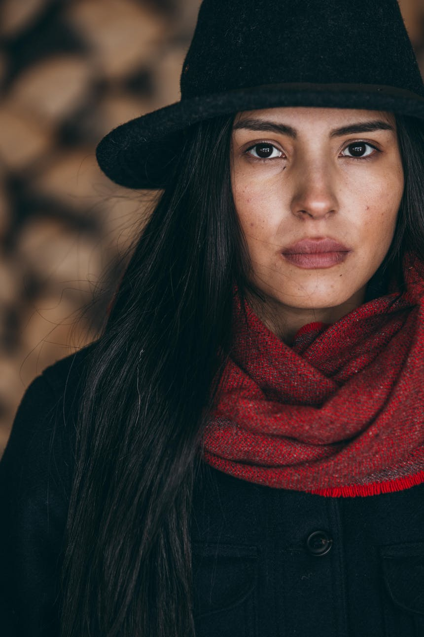 Keya portrait in black hat, red scarf and black jacket