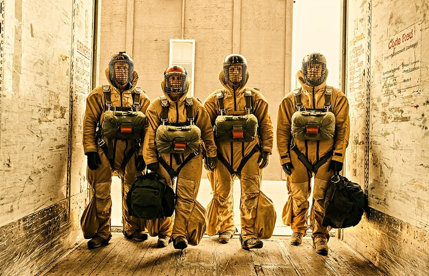 four smokejumpers in full uniform standing in white room