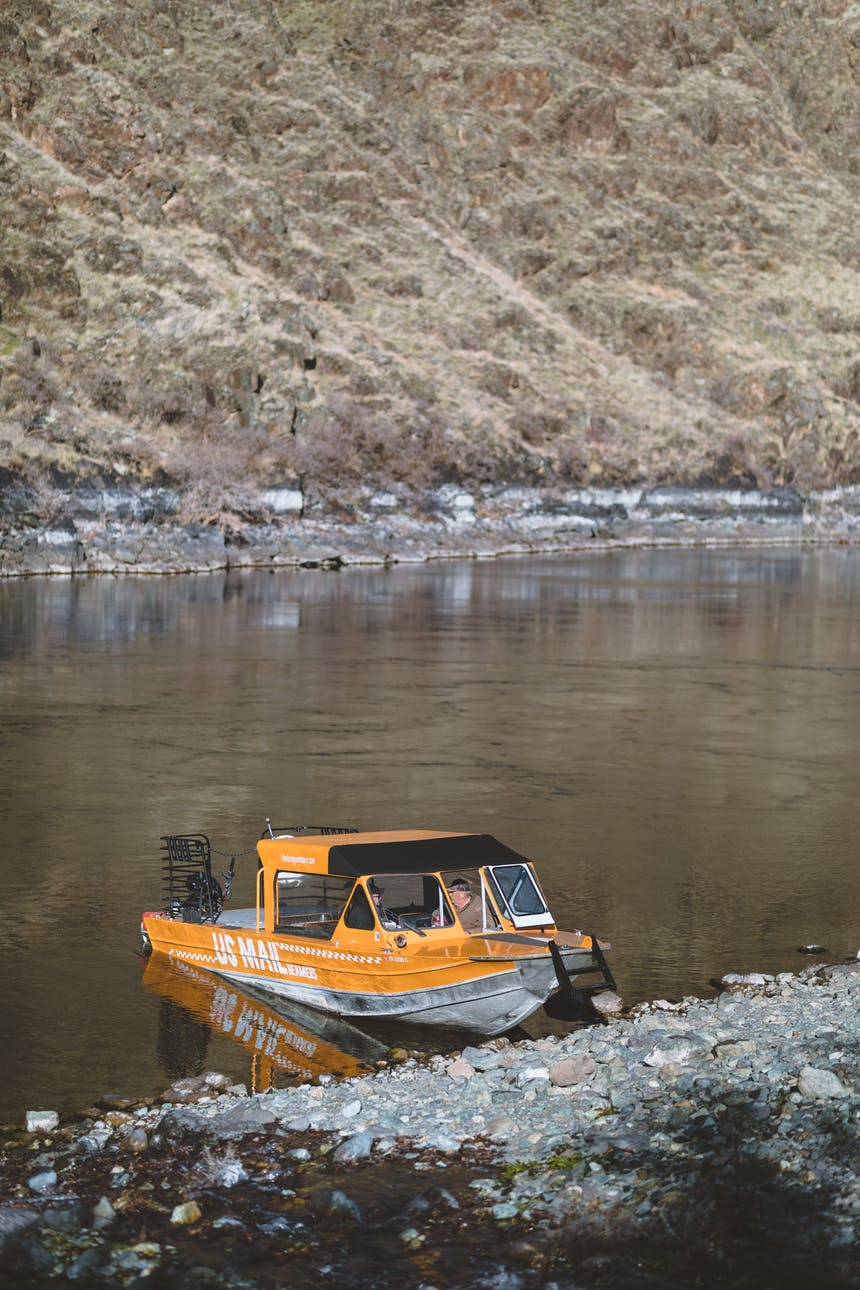 yellow motor boat grounded at rocky river bed