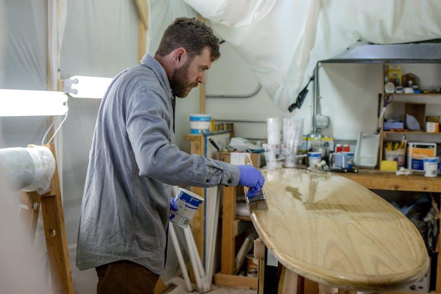 matthew painting a paddleboard