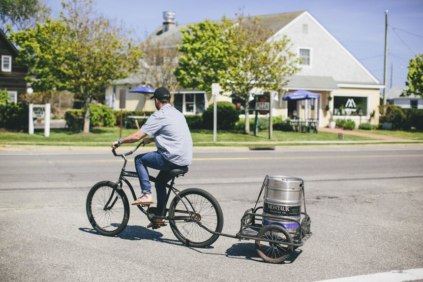 guy pulling a keg on a trailer with a bicycle