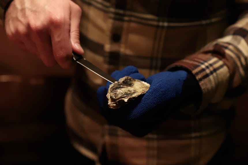 shucking oyster with shucking knife