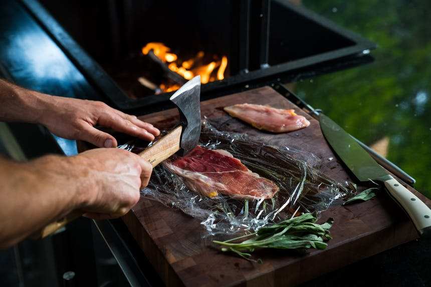 flattening meat with blunt end of axe