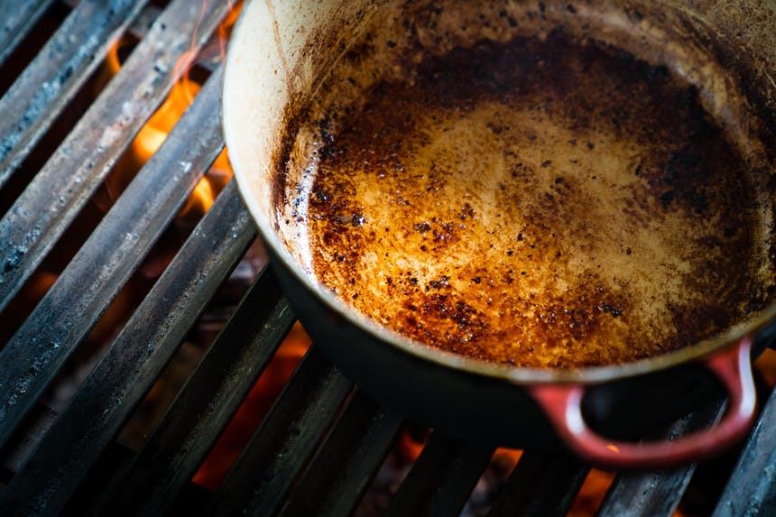 pot with glaze from meat drippings on grill grate