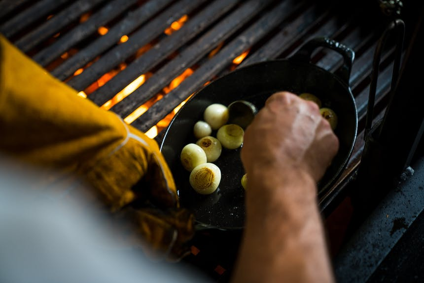 cooking onions in cast iron skillet on grill grates
