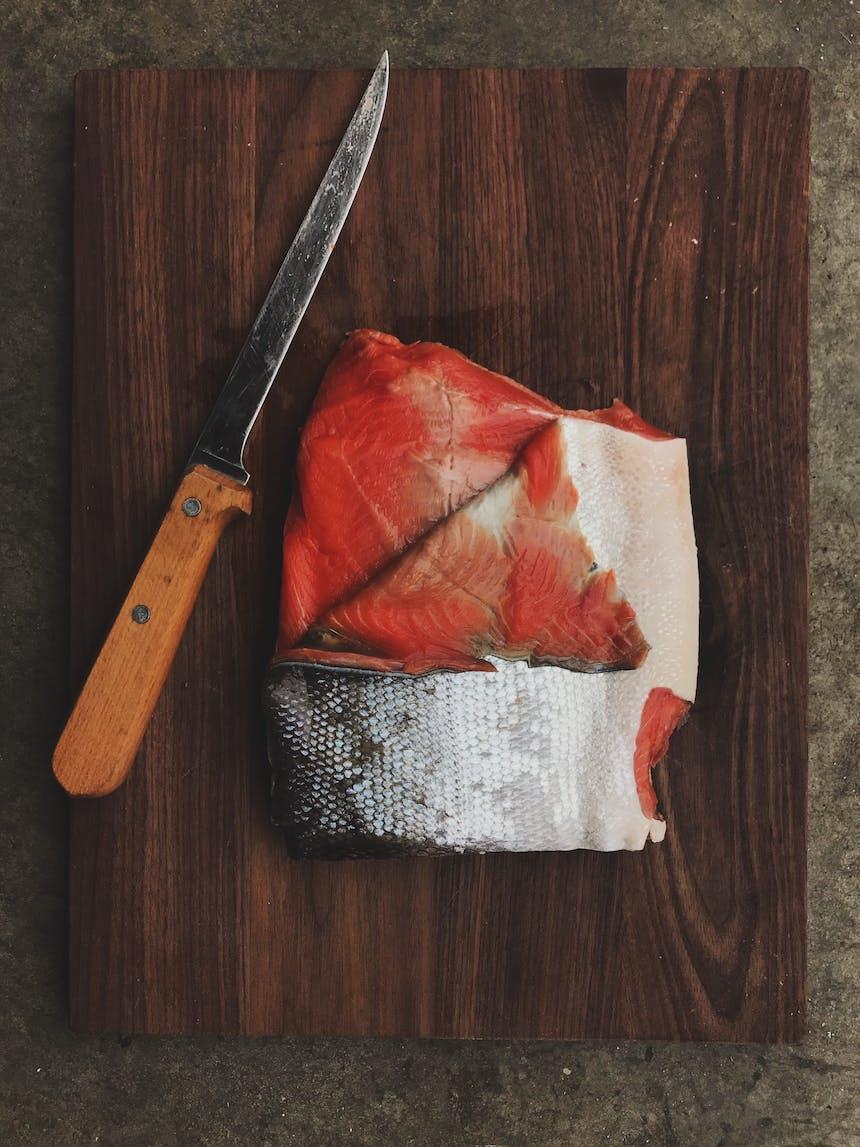 skinning a salmon filet on brown cutting board