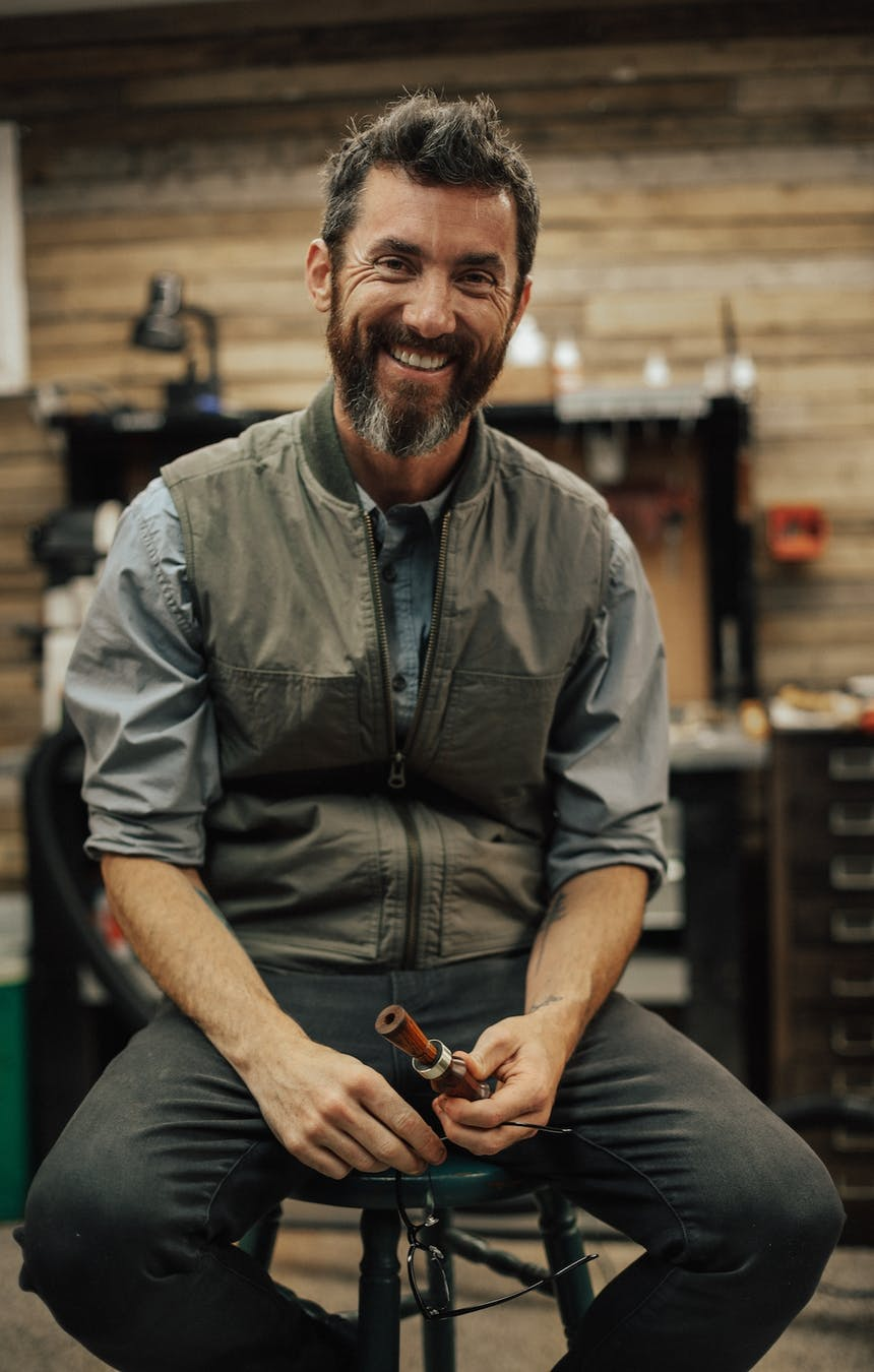 man sits in stool holding duck call in workshop