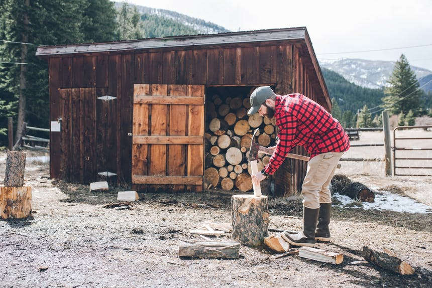 man in front of firewood shed chopping wood in pine forest