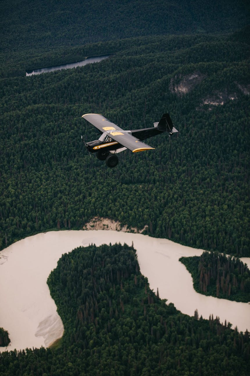 Sarah flying small black plane over river cutting through pine forest