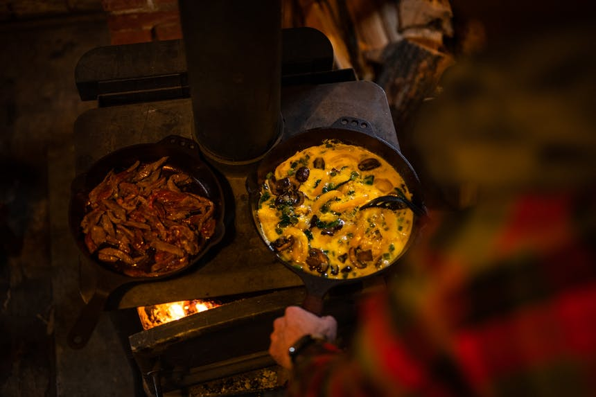 cooking scramble and steak on top of wood fired stove in cast iron skillet